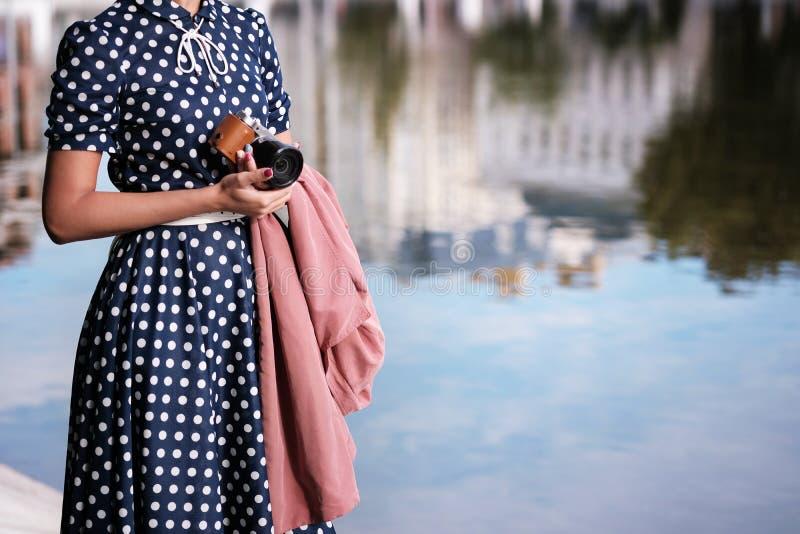 La fille de attente avec l'appareil-photo mirrorless aiment l'appareil-photo et le manteau de film dans des ses mains photo libre de droits