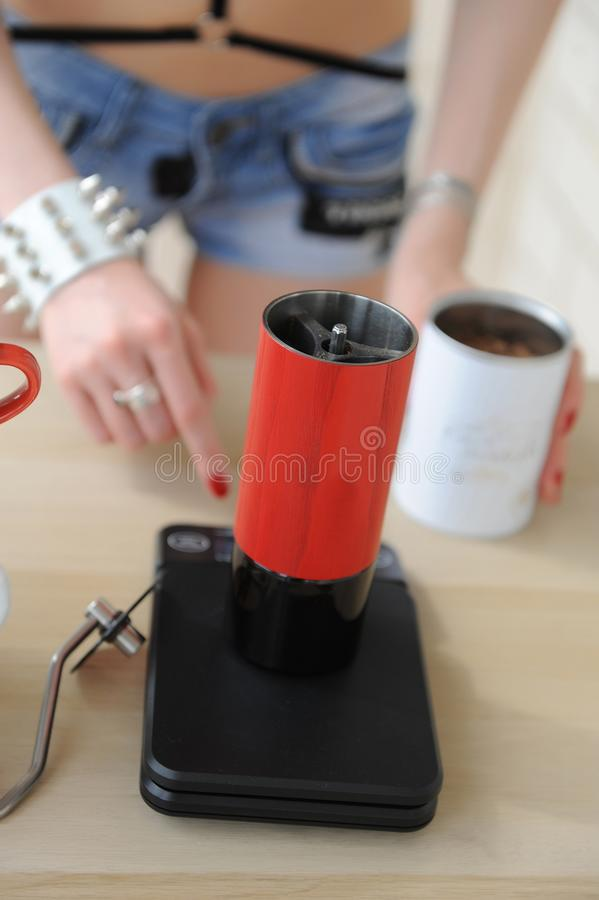 La fille de barman tourne sur les échelles électroniques avec la broyeur de café manuelle rouge Processus de Brewinf photos stock