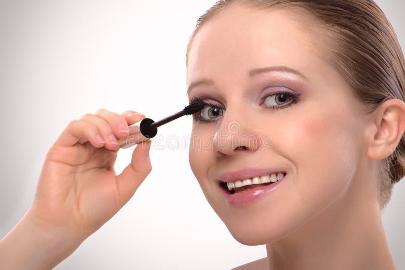 La fille de beauté peint le mascara de renivellement de cils image stock