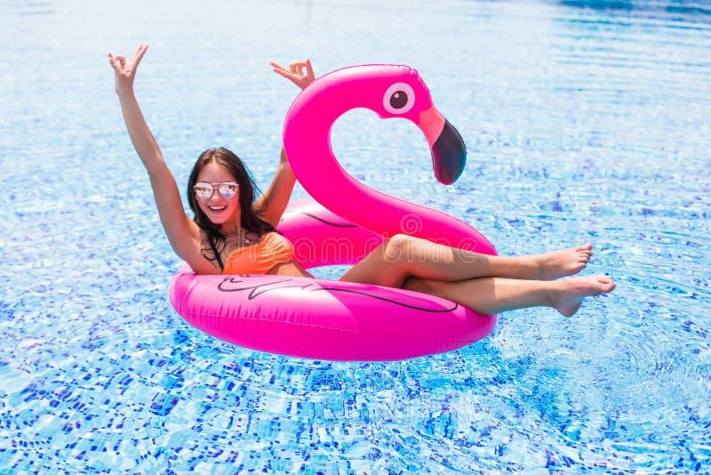 La fille de beauté s'assied sur les flamants gonflables de matelas dans la piscine photographie stock libre de droits