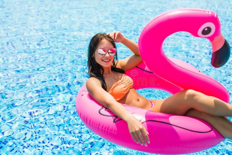 La fille de beauté s'assied sur les flamants gonflables de matelas dans la piscine images libres de droits