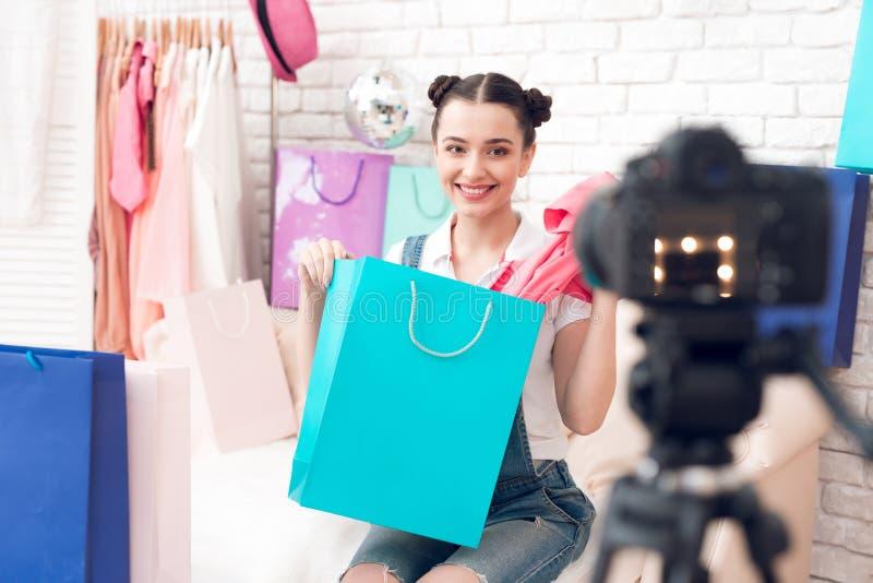La fille de blogger de mode avec composent l'article de tractions du sac coloré au sourire d'appareil-photo photos stock