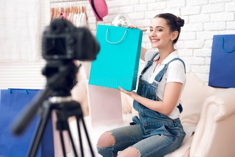 La fille de blogger de mode avec composent pour supporter le sac coloré au sourire d'appareil-photo photo stock
