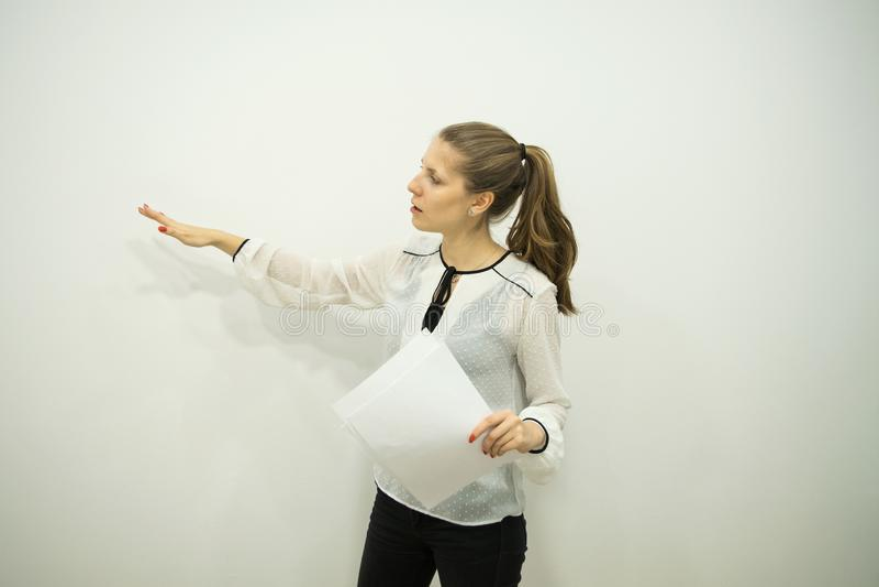 La fille de brune sur un fond blanc dit et indique le mur avec sa main droite photos stock