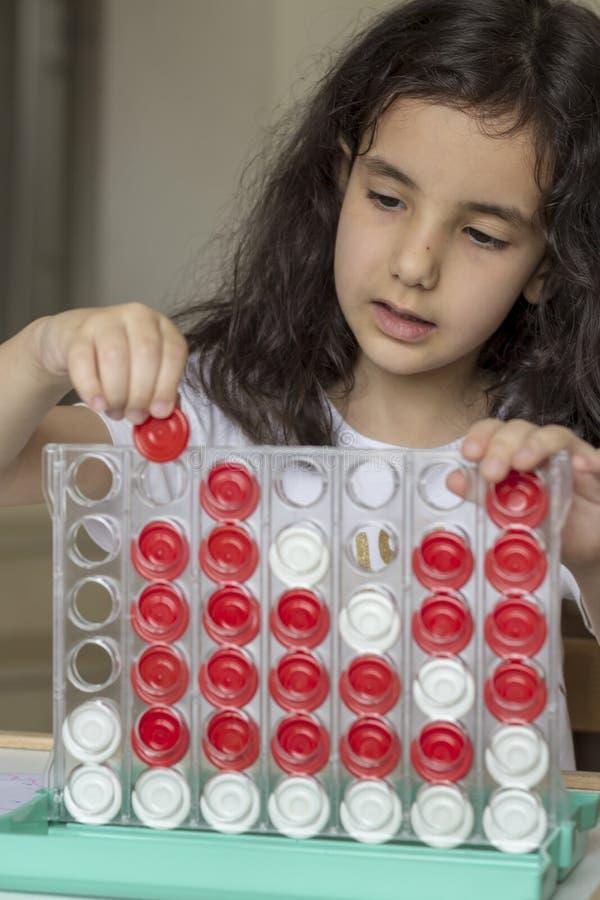 La fille de cheveux noirs jouant avec le boardgame image libre de droits