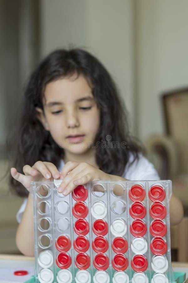 La fille de cheveux noirs jouant avec le boardgame photos libres de droits