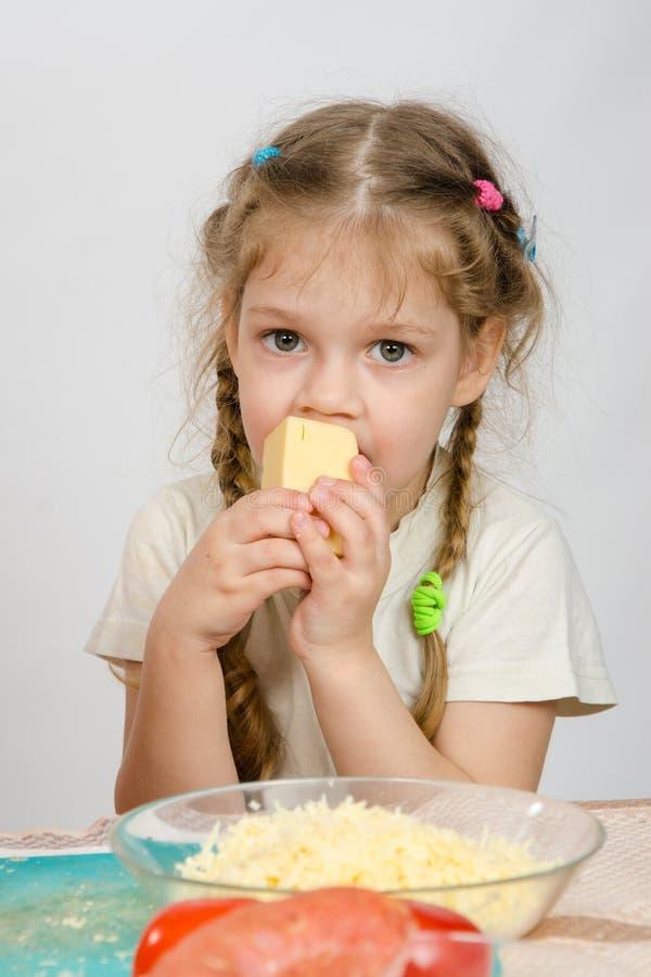 La fille de cinq ans avec des tresses mangeant du fromage à la table devant elle est un plat de fromage râpé photographie stock libre de droits