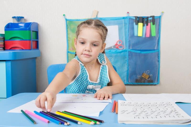 La fille de cinq ans choisissent le crayon droit faisant la peinture photos libres de droits