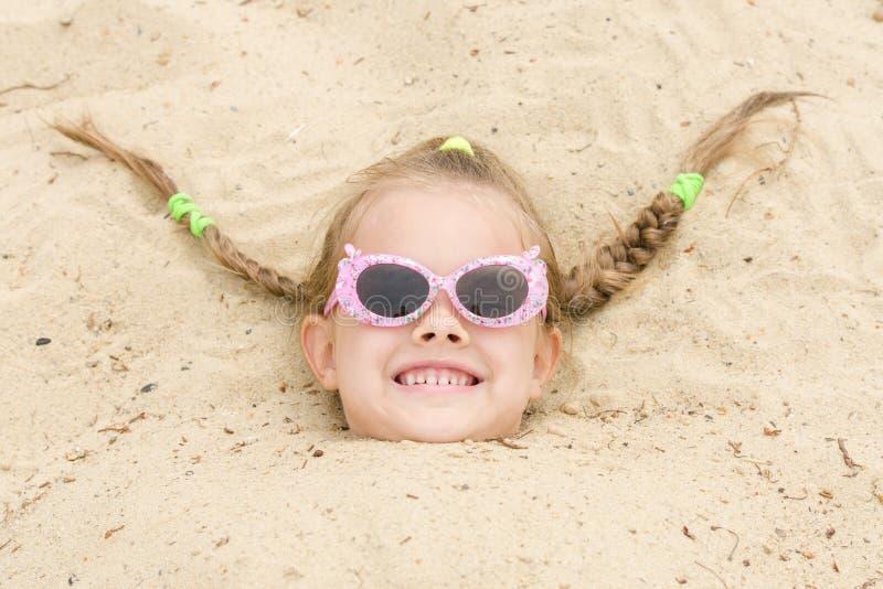 La fille de cinq ans est tombée endormi sur sa tête dans le sable photo libre de droits