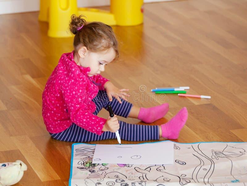 La fille de deux ans dessine et colore sur le plancher photo stock