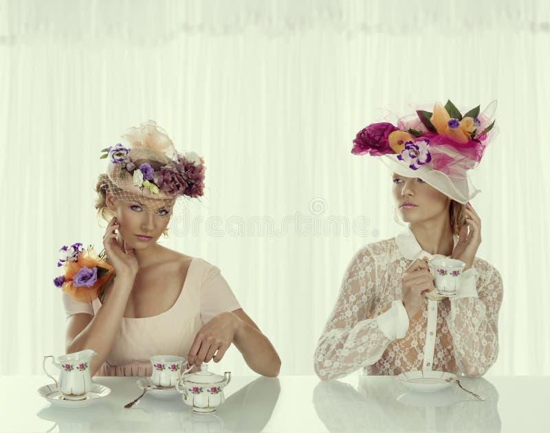 La fille de deux blondes avec le service à thé classique prend le thé images libres de droits