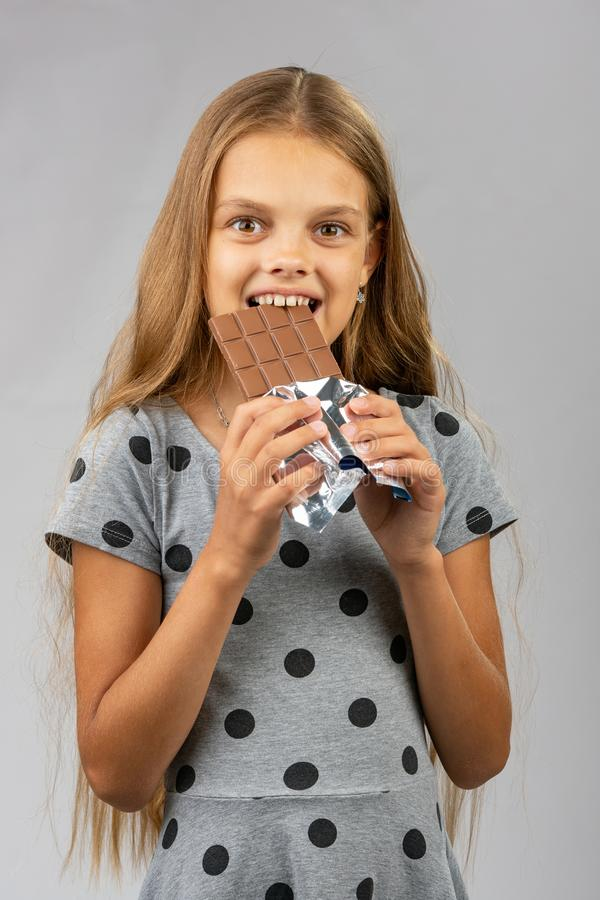 La fille de dix ans mord le chocolat et examine heureusement le cadre photos stock