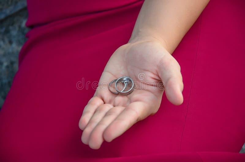 La fille de fiançailles dans la robe rouge de robe se tient dans sa main deux épousant image stock