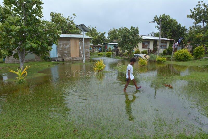 La fille de Fijian marche au-dessus de la terre inondée aux Fidji images stock