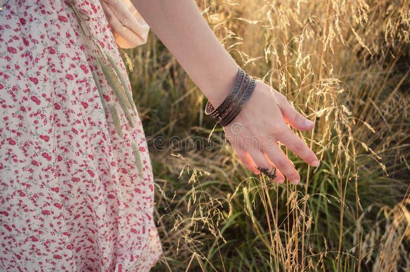 La fille de Forest Mori court sa main par l'herbe jaune images stock