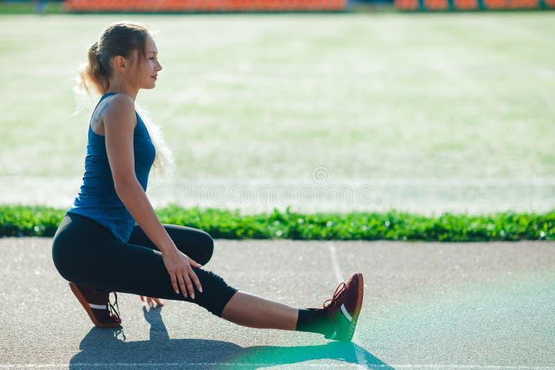 La fille de forme physique dans une chemise bleue et des guêtres faisant la routine d'échauffement sur le sadium avant la formati images stock