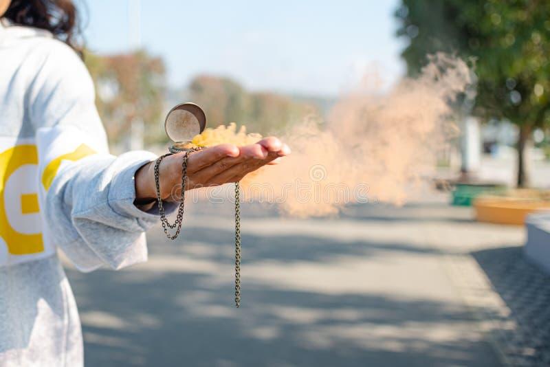 la fille a de la fumée colorée qui se répand de sa montre de poche dans la main valeur horaire mobile poussière fumée eau de fumé photo libre de droits