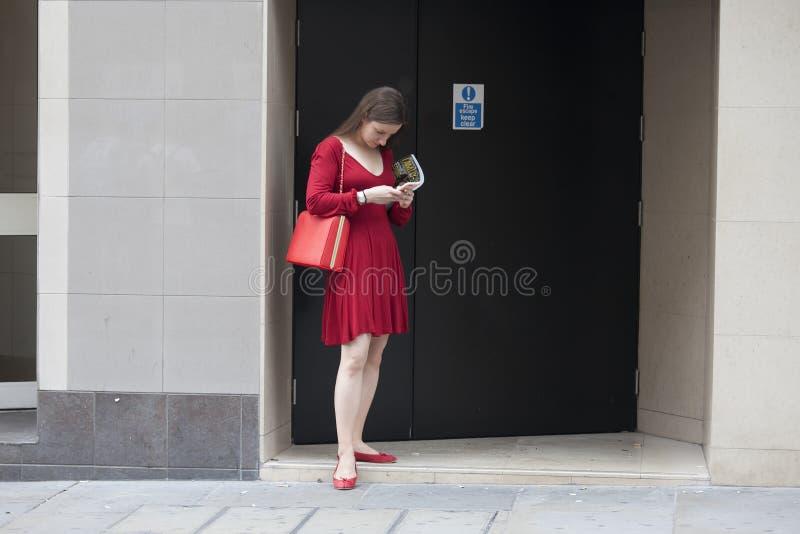 La fille de hippie dans la robe rouge s'est habillée dans le style frais de Londonien tenant le mur proche image stock