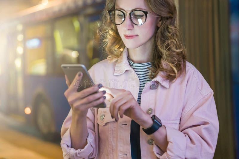La fille de hippie en verres se tient sur la rue de nuit et le smartphone d'utilisations, écran tactile avec le doigt photos libres de droits