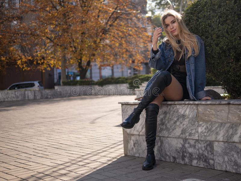 La fille de jeune adolescent avec les cheveux bien-toilettés avec de belles longues jambes s'assied sur la rue avec ses jambes c images stock