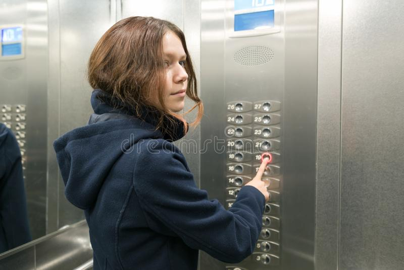 La fille de jeune adolescent dans l'ascenseur, appuie sur le bouton d'ascenseur photos stock