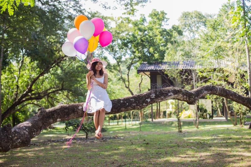 La fille de jeune adolescent s'asseyant sur l'arbre et se tenant monte en ballon ? disposition images libres de droits