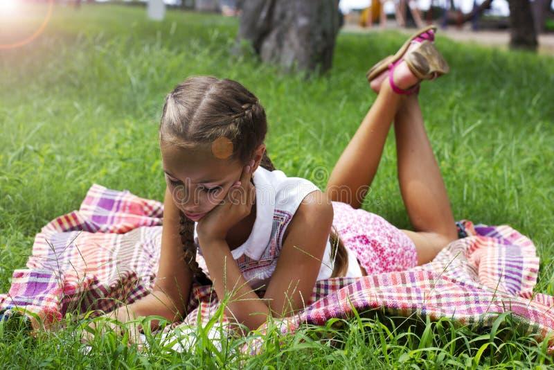 La fille de jeune adolescent se trouve sur l'herbe verte et a lu le livre photo libre de droits