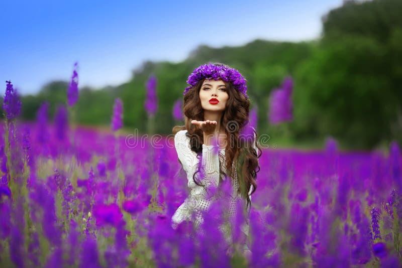 La fille de l'adolescence de brune de Beautidul envoie un baiser d'air au-dessus des fleurs sauvages image libre de droits