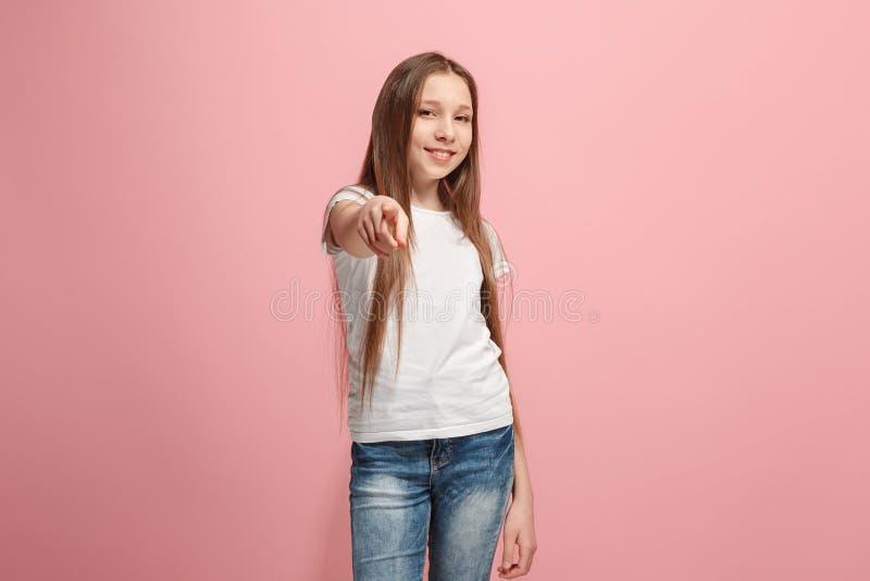 La fille de l'adolescence heureuse indiquant vous, portrait en buste de plan rapproché sur le fond rose photo stock