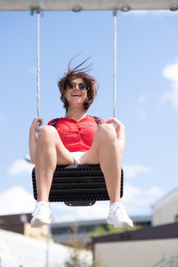 la fille de l'adolescence heureuse ont l'amusement sur la fusée du soleil d'oscillation photographie stock libre de droits