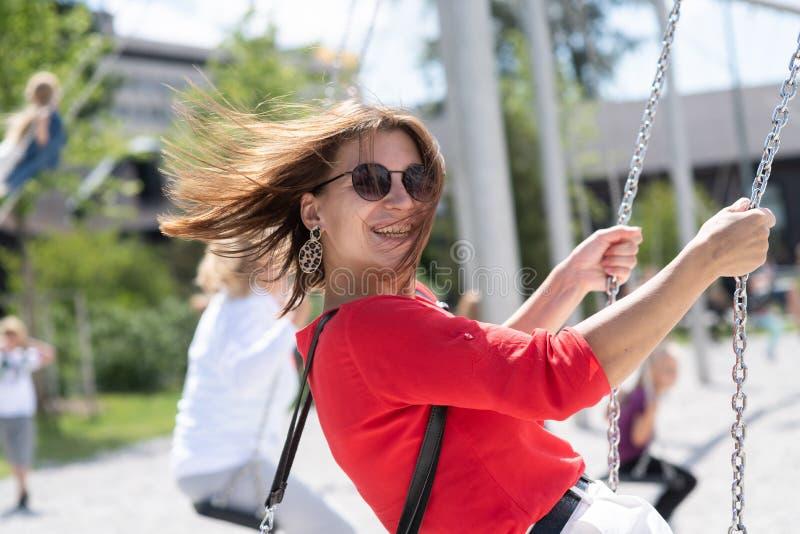 la fille de l'adolescence heureuse ont l'amusement sur la fusée du soleil d'oscillation photos libres de droits