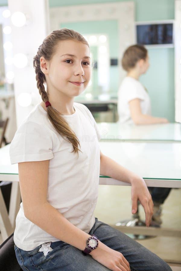 La fille de l'adolescence mignonne avec la longue tresse habillée dans le T-shirt blanc s'assied sur la chaise dans le vestiaire images libres de droits