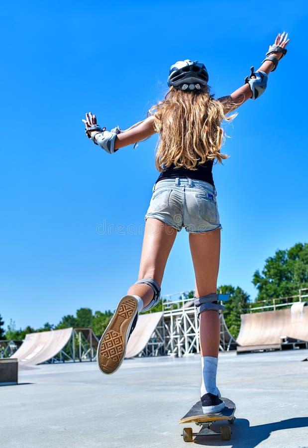 La fille de l'adolescence monte sa planche à roulettes photos libres de droits