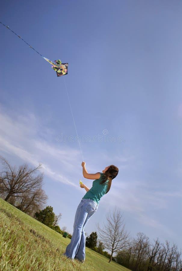 La fille de l'adolescence pilote le cerf-volant images libres de droits