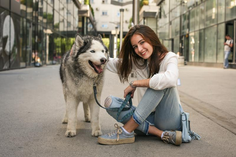 La fille de l'adolescence pose à l'appareil-photo avec son chien de traîneau photo libre de droits