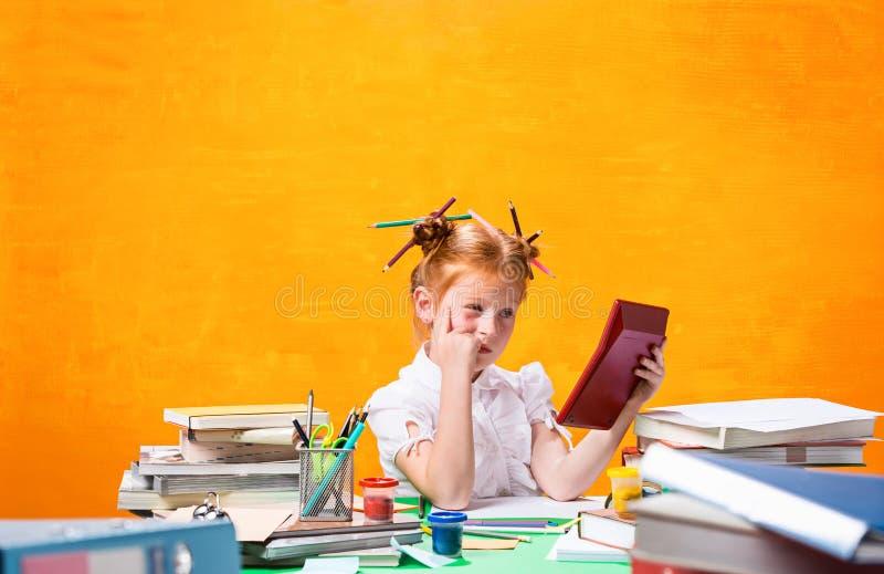 La fille de l'adolescence rousse avec le sort de livres à la maison Projectile de studio image stock