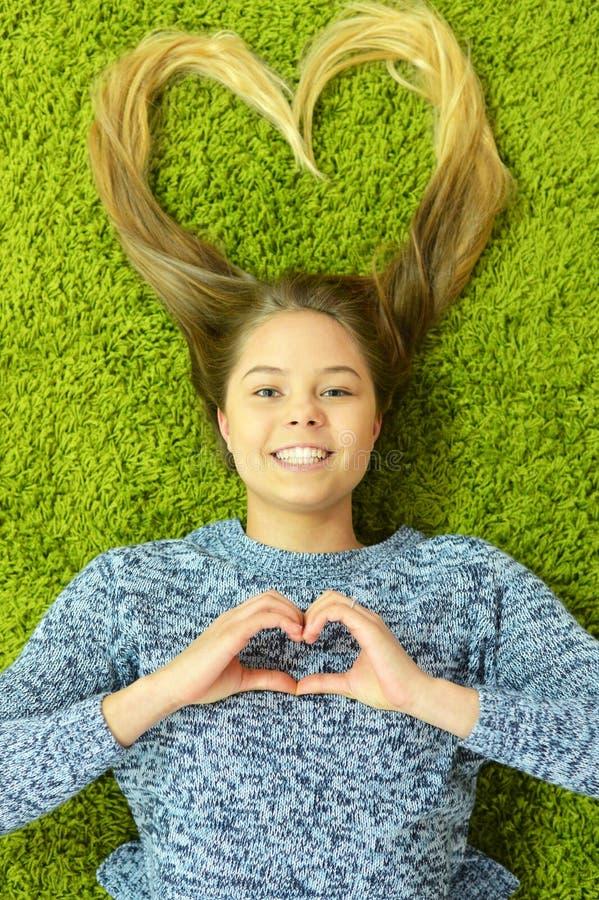 La fille de l'adolescence se trouve sur le tapis photo stock