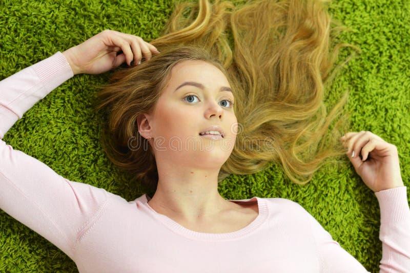 La fille de l'adolescence se trouve sur le tapis photographie stock libre de droits