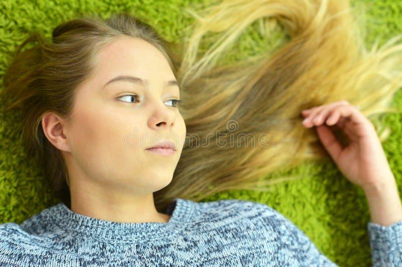La fille de l'adolescence se trouve sur le tapis photo libre de droits