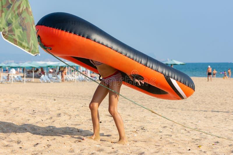 La fille de l'adolescence traîne sur elle de retour un grand bateau gonflable sur une plage sablonneuse image libre de droits