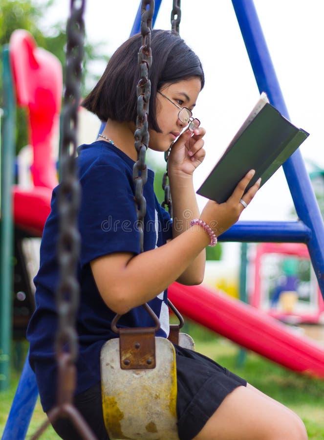 La fille de lecture balance des chaînes images stock