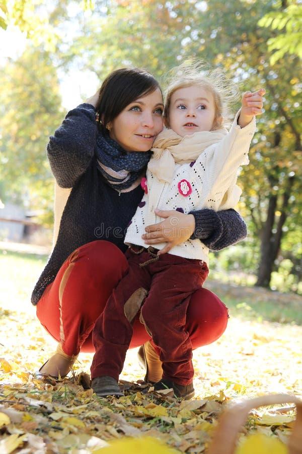 La fille de mère et de bébé discutant parmi l'automne se garent photos stock
