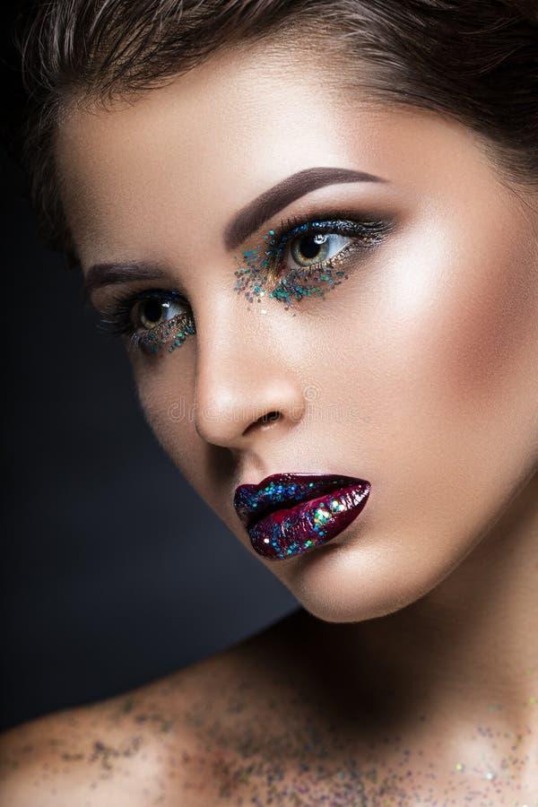 La fille de mannequin de beauté avec lumineux composent Portrait d'art de mode avec des scintillements en gros plan photo libre de droits