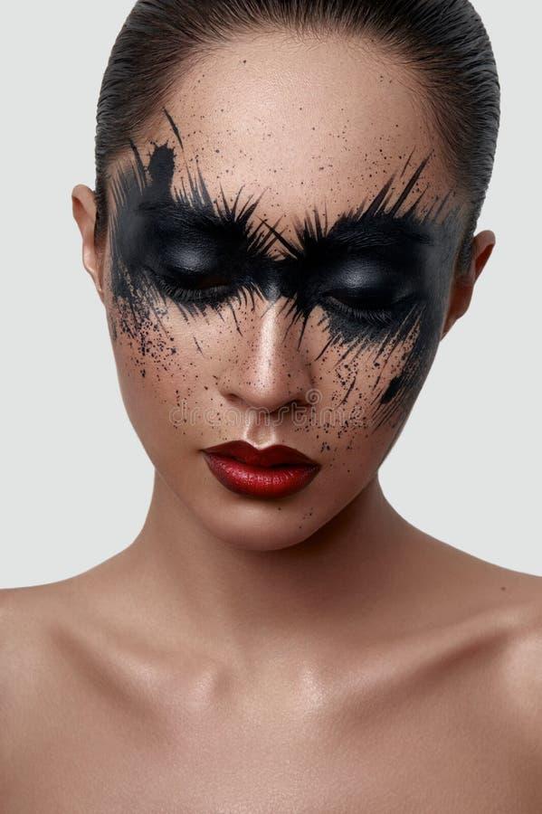 La fille de mode avec la peinture noire éclabousse sur son visage photo libre de droits