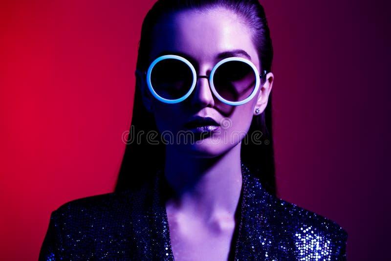 La fille de mode avec de longs cheveux et lunettes de soleil rondes dans une robe brillante noire pose dans la lampe au néon dans photographie stock