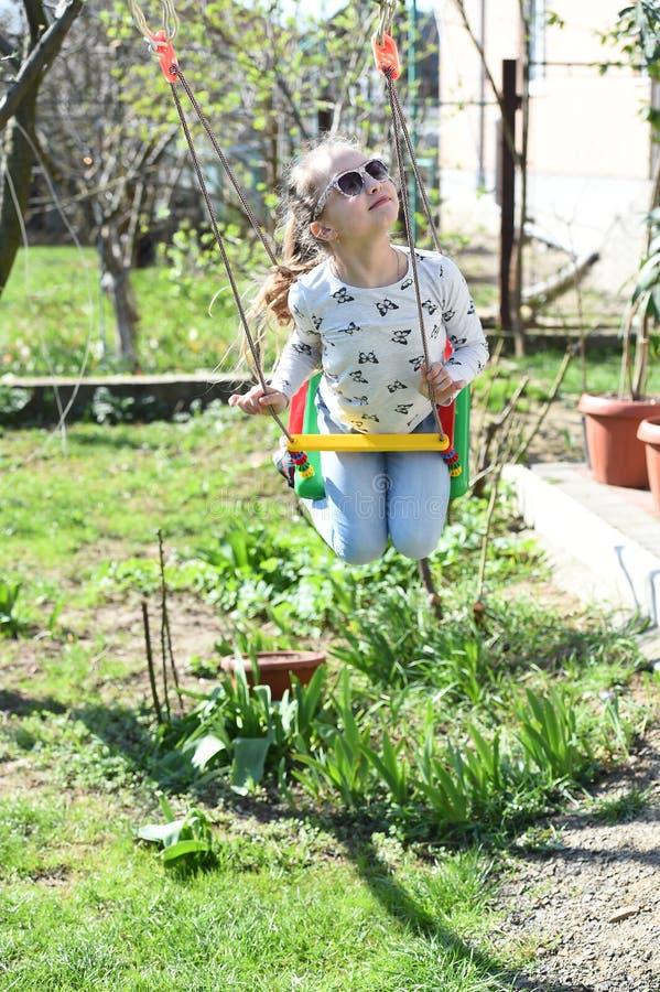 La fille de mode dans des lunettes de soleil ont plaisir à balancer le jour ensoleillé Petit enfant sur l'oscillation dans la cou image libre de droits