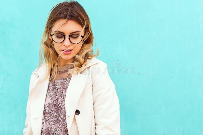 La fille de mode en verres ronds tient la pose près d'une turquoise wal photographie stock libre de droits