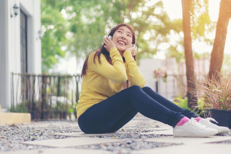 La fille de mode de vie apprécient la musique de écoute et détendent l'été heureux dans le thepark image libre de droits