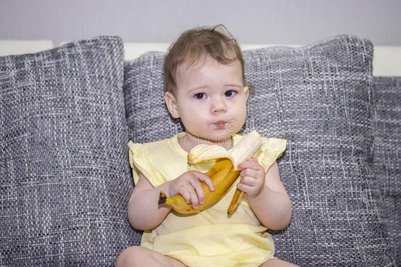 La fille de 10 mois mange une banane mûre se reposant sur un sofa gris Un petit enfant mange des fruits exotiques Fille en jaune  photos libres de droits