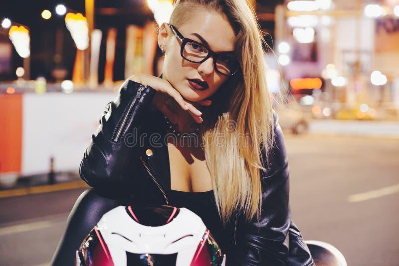 La fille de motard dans un cuir vêtx sur une moto photographie stock libre de droits